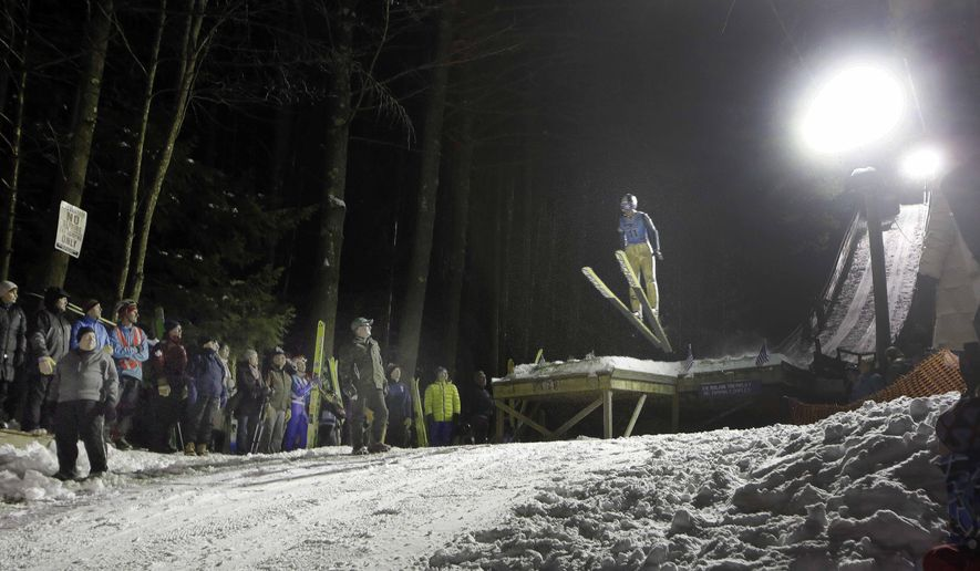 In this photo taken Wednesday Feb. 4, 2015 fans watch as a high school ski jumper competes in Newport, N.H. The state is the only place in the nation that still offers ski jumping as a competitive sport for high-schoolers.(AP Photo/Jim Cole)