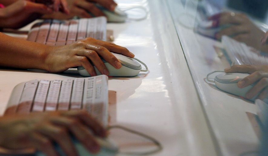 FILE - In this June 16, 2013 file photo, users browse the Internet in an underground station in Hong Kong. As hacks abound, some companies are testing workers' security-savvy by sending spoof phishing emails to see who bites. (AP Photo/Kin Cheung, File)