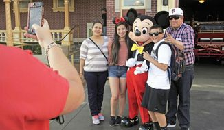 In this Jan. 22, 2015, file photo, visitors pose with Mickey Mouse at Disneyland in Anaheim, Calif. (AP Photo/Jae C. Hong, File)
