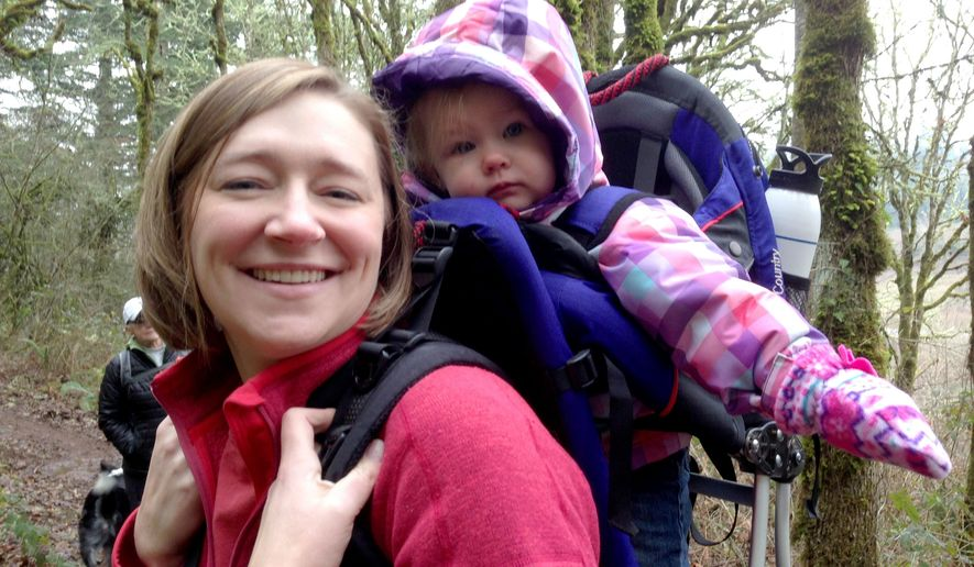 This Dec. 2014 photo provided by Amy Rockwell, Kristi Neznanski carries her daughter Hazel in a pack during a Salem Hike It Baby outing at the Croisan Trail system in South Salem, Ore.  The group called Hike It Baby, which recently opened a branch in Salem, is encouraging new parents to get outdoors by offering a supportive atmosphere on organized weekly hikes.  A collection of 118 people are part of the Salem group, and during the last two weekends, they've had hikes at the Croisan Trail system in South Salem and Kezier Rapids Park.   (AP Photo/Statesman-Journal, Courtesy of Amy Rockwell)
