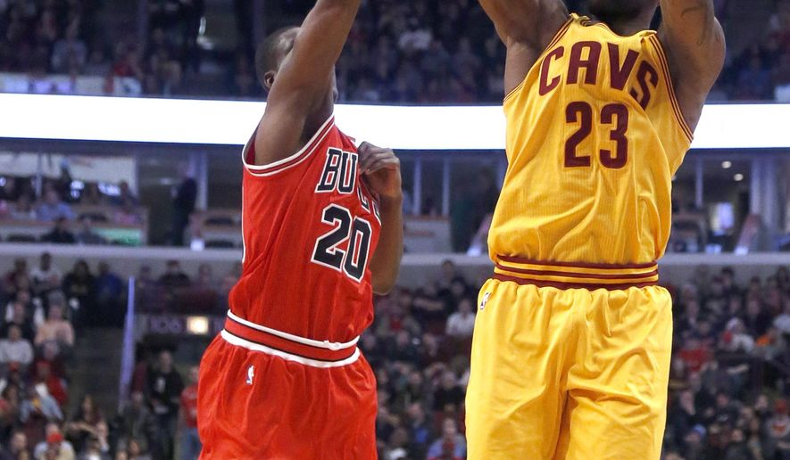 Cleveland Cavaliers forward LeBron James (23) shoots over Chicago Bulls forward Tony Snell (20) during the first half of an NBA basketball game Thursday, Feb. 12, 2015, in Chicago. (AP Photo/Charles Rex Arbogast)