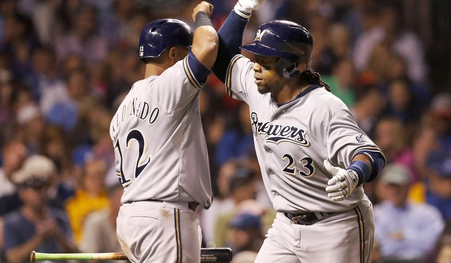 FILE - In this Aug. 13, 2014, file photo, Milwaukee Brewers' Martin Maldonado (12) greets Rickie Weeks at home after Weeks' home run off Chicago Cubs starting pitcher Tsuyoshi Wada, during the seventh inning of a baseball game in Chicago. Former All-Star Weeks and the Seattle Mariners have agreed to a $2 million, one-year contract, according to a person with knowledge of the negotiations.  (AP Photo/Charles Rex Arbogast, File)