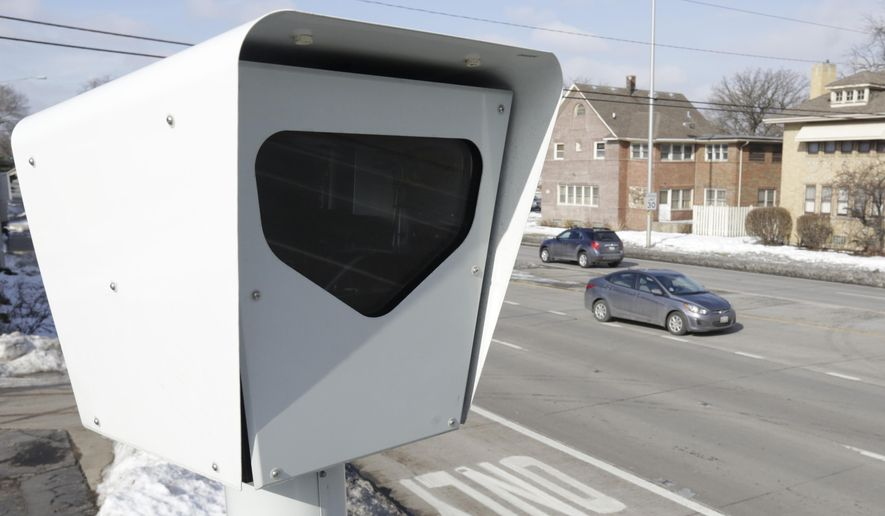 In this file photo taken Tuesday, Feb. 10, 2015, cars pass by a red light camera in Blue Island, Ill.  (AP Photo/M. Spencer Green) **FILE**
