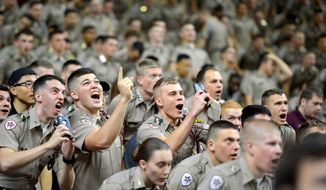 Members of the Texas A&M University Corps of Cadets take selfies as they are features on big screen at at Reed Arena in College Station, Texas on Wednesday, Feb. 11, 2015, during the first half of a NCAA college basketball game between Georgia and Texas A&M. Georgia won 62-53. (AP Photo/College Station Eagle, Sam Craft)
