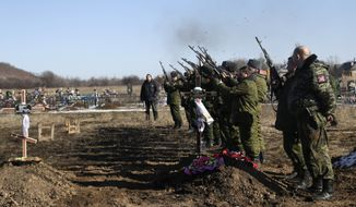 Russia-backed separatist fighters shoot in the air to pay respects to their comrade during a funeral at a cemetery in the east Ukrainian village of Mospino, near the city of Donetsk, Ukraine, on Thursday, Feb. 12, 2015. The militiaman was killed during recent fighting between Russia-backed separatists and government forces. Guns will fall silent, heavy weapons will pull back from the front, and Ukraine will trade a broad autonomy for the east to get back control of its Russian border by the end of this year under a peace deal hammered out Thursday after all-night negotiations between Russia, Ukraine, France and Germany. (AP Photo/Petr David Josek)