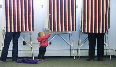 14-month-old Zoe Buck checks out an empty voting booth as at her mother, Julie Buck, votes at left on Nov. 4 at the Alaska Zoo polling place in Anchorage, Alaska. (Associated Press)