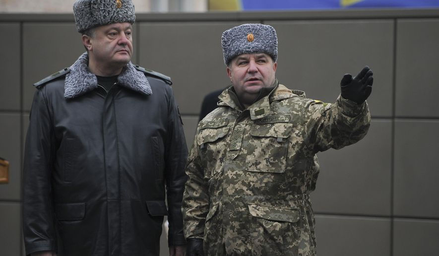 Ukraine's President Petro Poroshenko, left, and defence minister Stepan Poltorak, talk at the National Guard Training Center in Novy Petrivtsy, Ukraine, Friday, Feb. 13, 2015.  (AP Photo/ Andrew Kravchenko, Pool)