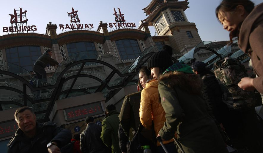 Workers clean the windows of the main entrance of the Beijing railway station as travelers wait, in Beijing, Friday, Feb. 13, 2015. Millions of Chinese will be traveling to their hometowns to celebrate the Lunar New Year on Feb. 19 this year which marks the Year of the Sheep on the Chinese zodiac. (AP Photo/Andy Wong)
