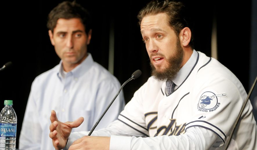 James Shields wears his new San Diego Padres' jersey as he answers after signing a four year contract with the Padres Wednesday, Feb. 11, 2015, in San Diego. General manager A.J. Preller, left,  listens. (AP Photo/Lenny Ignelzi)