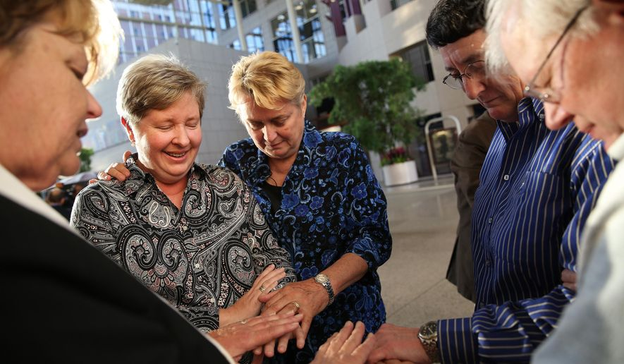 Kim Gebauer, left, and Regina Gebauer both of Daphne, Ala., get married in a double wedding with Peggy Belcher, second from right, and her partner Louise Lynn, both of Mobile, Ala., at Government Plaza in Mobile, Ala., Thursday Feb. 12, 2015. The Rev. Sandy O'Steen of Cornerstone Metropolitan Community Church in Mobile, Ala., officiated. (AP Photo/Mobile Press-Register, Sharon Steinmann)