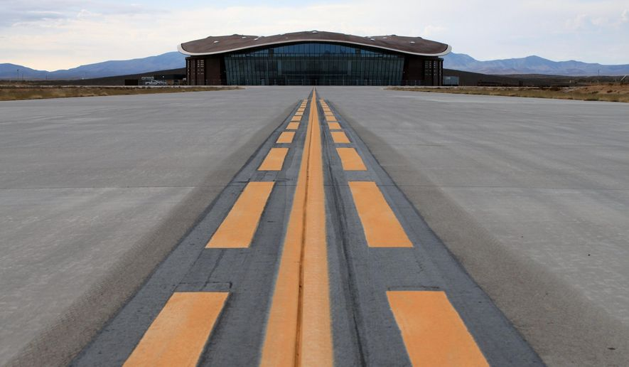 FILE-This Dec. 9, 2014, file photo shows the taxiway leading to the hangar at Spaceport America in Upham, N.M.   Sen. George Munoz has proposed legislation that calls for selling the futuristic hangar, the nearly two-mile-long runway and the 18,000 acres that come with it.  (AP Photo/Susan Montoya Bryan)