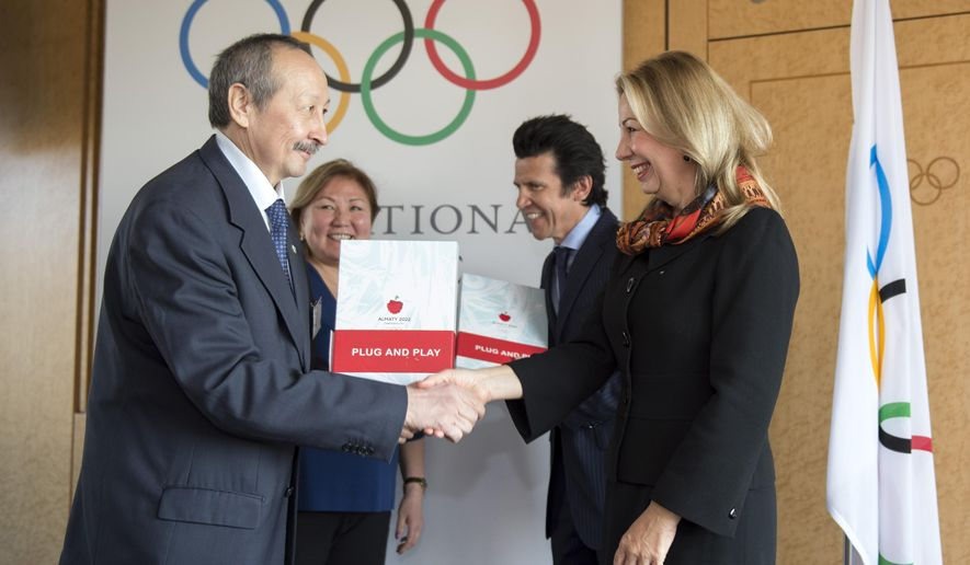 FILE -  This is a Tuesday, Jan.  6, 2015  file photo of members of the Almaty Olympic Winter Games 2022 candidate city, from left, Timur Dossymbetov, Secretary General,National Olympic Committee of the Republic of Kazakhstan, Zauresh Amanzhilova, Vice Mayor of Almaty City, shake hands next to IOC Sports Director Christophe Dubi and IOC head of Olympic bid city coordination Jacqueline Barrett at the International Olympic Committee (IOC) headquarters before submitting the candidature bid in Lausanne, Switzerland. An International Olympic Committee panel arrved Friday Feb. 13, 2015 to visit the Kazakh city of Almaty to assess its bid for the 2022 Winter Games.   (AP Photo/Keystone,Anthony Anex, File)