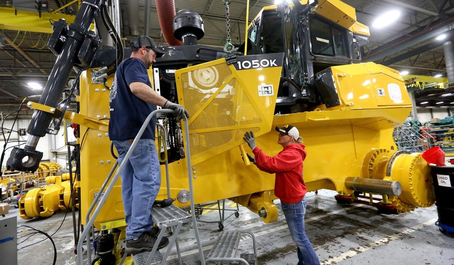 Rick Ring, left, and Corinne Schmitt-Bries attach a panel to a John Deere 1050K Crawler Dozer Wednesday, Feb. 11, 2015, at John Deere Dubuque Works in Dubuque, Iowa.  John Deere has recently laid off hundreds of workers in the Midwest, but it has added jobs at its factory in Dubuque, where the company manufactures huge vehicles for construction and forestry.  (AP Photo/Telegraph Herald, Jessica Reilly)