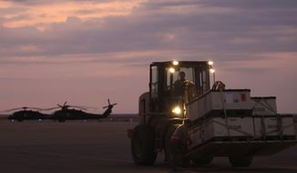 U.S. army soldiers load equipments onto an aircraft, not seen, as they prepare to make the journey home at al-Asad airbase west of Baghdad, Iraq, on Nov. 1 , 2011. (AP Photo/Khalid Mohammed) **FILE**