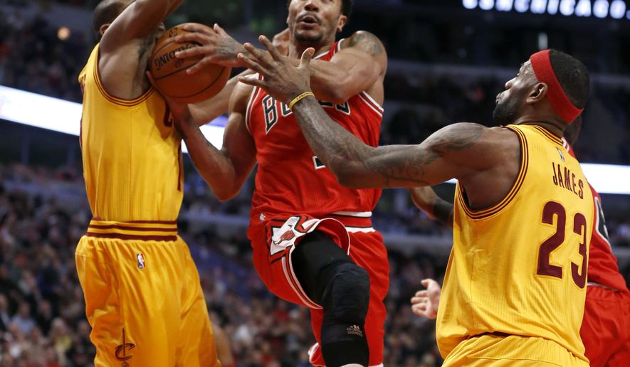 Chicago Bulls guard Derrick Rose (1) drives and scores past Cleveland Cavaliers' James Jones, left, and LeBron James during the second half of an NBA basketball game Thursday, Feb. 12, 2015, in Chicago. The Bulls won 113-98. (AP Photo/Charles Rex Arbogast)