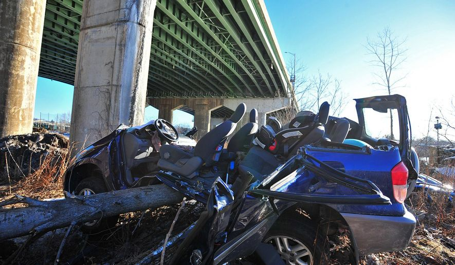 A SUV that catipulted off an Interstate 80 bridge overhead lies in a heap along the banks of the Hackensack River, Friday, Feb. 13, 2015, in Hackensack, N.J. The driver, swerving to avoid striking another vehicle on a highway, hit a snowbank along a guardrail and catapulted 60 feet off a bridge. Incredibly, authorities say, the two occupants suffered only minor injuries, and the vehicle landed upright. (AP Photo/The Record of Bergen County, Marko Georgiev) ONLINE OUT; MAGS OUT; TV OUT; INTERNET OUT;  NO ARCHIVING; MANDATORY CREDIT