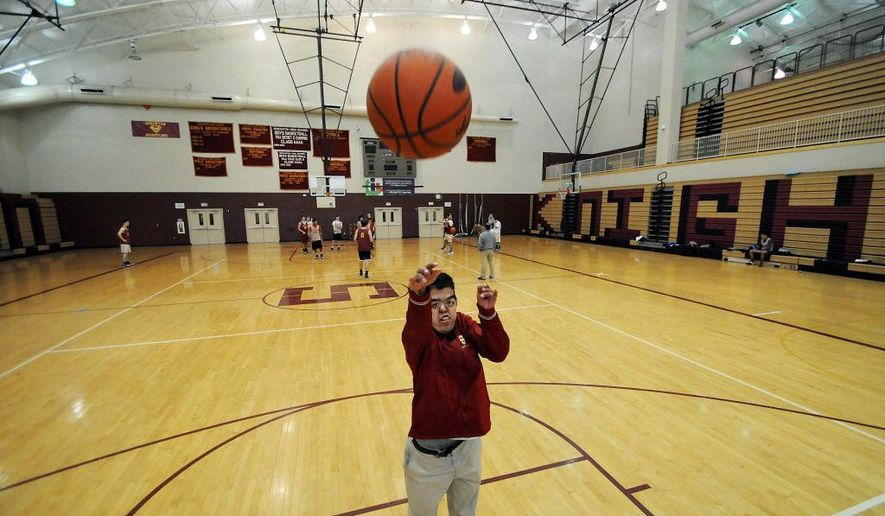 In this Feb. 11, 2015 photo, Scranton High School senior and boys basketball team manager Billy Foster shoots in Scranton, Pa. Known more for being the Scranton team manager and inspirational leader, the senior was the toast of the school Wednesday after scoring eight fourth-quarter points Tuesday in the Knights' loss to Abington Heights. (AP Photo/The Times & Tribune, Butch Comegys)