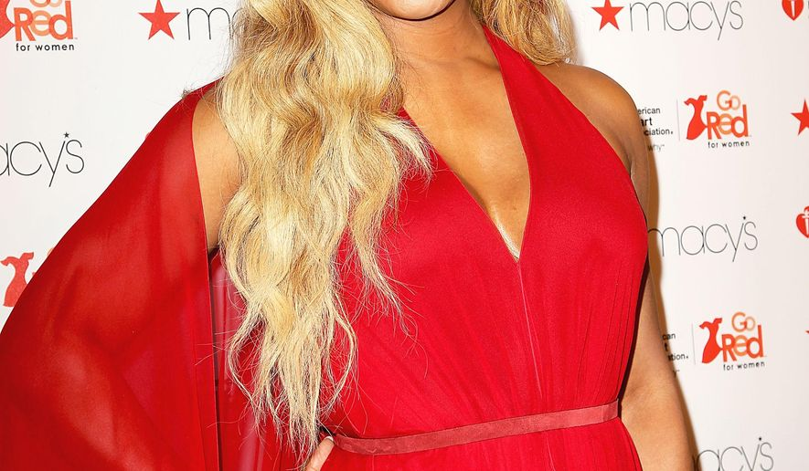 In this image released by Starpix, Laverne Cox poses in a Donna Karan dress at the Go Red for Women Red Dress Fashion Show, Thursday, Feb. 12, 2015, at Lincoln Center in New York. (AP Photo/Starpix, Aurora Rose)