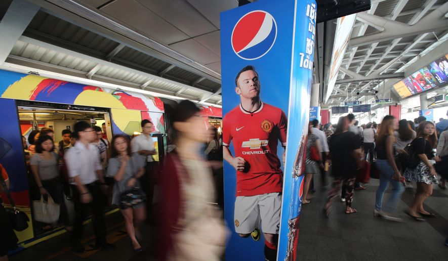 Passengers walk past an advertisement for Manchester United's Wayne Rooney in Bangkok, Friday, Feb. 13, 2015. The popularity of English football in Thailand has led Thai investors to leverage their brands by buying English clubs.(AP Photo/Sakchai Lalit) ** FILE **