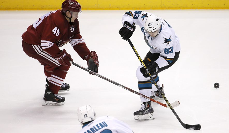 Arizona Coyotes' Andrew Campbell (45) and San Jose Sharks' Matt Nieto (83) vie for the puck during the first period of an NHL hockey game, Friday, Feb. 13, 2015, in Glendale, Ariz. (AP Photo/Matt York)