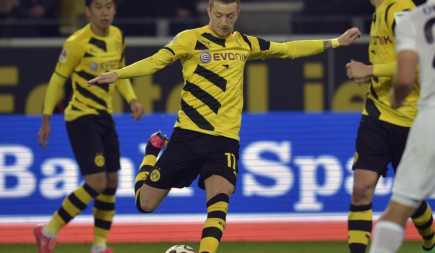 Dortmund's Marco Reus kicks the ball during the German Bundesliga soccer match between Borussia Dortmund and FSV Mainz in Dortmund, Germany, Friday, Feb. 13, 2015. (AP Photo/Martin Meissner)