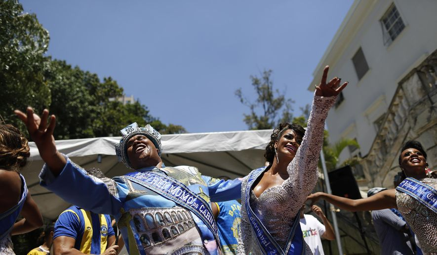 The 2015 Carnival King, King Momo, Wilson Dias da Costa Neto, left, and the Carnival Queen Clara Paixao, gesture at a ceremony marking the official start of Carnival in Rio de Janeiro, Brazil, Friday, Feb. 13, 2015. (AP Photo/Leo Correa)
