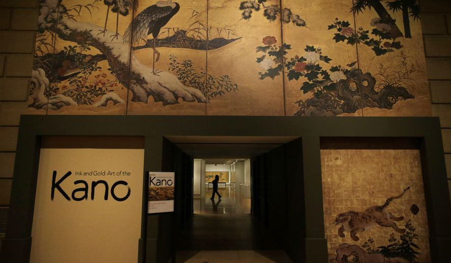 "A museum guard walks through an exhibit of Japanese paintings before a press preview at the Philadelphia Museum of Art, Friday, Feb. 13, 2015, in Philadelphia.The exhibit entitled, ""Ink and Gold: Art of the Kano"" is scheduled to run from Feb. 16 through May 10. (AP Photo/Matt Slocum)"