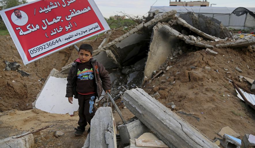 "In this Tuesday, Nov. 25, 2014 photo, Khaled Malakeh, 6, stands on the rubble of his family house in the Zeitoun neighborhood in Gaza City, destroyed in an Israeli airstrike July 9. The attack killed his father, a Hamas policeman, his mother and two siblings. The sign in Arabic reads, ""House of martyr Mostafa Jamal Malakeh (Abu Khaled)."" (AP Photo/Adel Hana)"