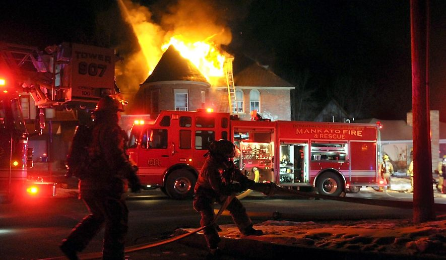 Firefighters work to put out a blaze on South Broad Street in Mankato, Minn., Thursday, Feb. 12, 2015. Five apartments in a Mankato house have been evacuated following a blaze that apparently started in a fireplace chimney. (AP Photo/The Mankato Free Press, Pat Christman)