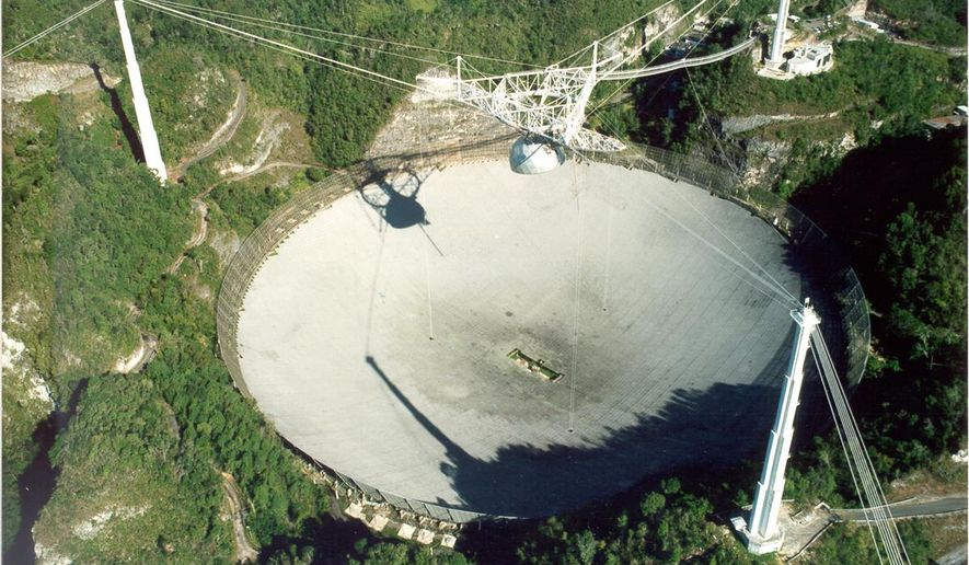 """This undated handout photo provided by Seth Shostak, SETI Institute, shows the Arecibo radio telescope in Puerto Rico. The world's largest single antenna, it has a million watt transmitter. Astronomers have their own cosmic version of the single person's Valentine's Day dilemma: Do you wait for that interesting person to call you or do you make the call yourself and risk getting shot down. Their version involves E.T. Instead of love, astronomers are looking for life out there in the universe. For decades, astronomers have sat by their telescopes, listened and waited for a call from E.T. only to be left alone. So now some of them want to aim their best radars and lasers out to the sky to say """"We're here, call us"""" to the closest few thousand worlds. They can bring us all sorts of new technologies and answers to burning questions, some hope. (AP Photo/Seth Shostak, SETI Institute)  **FILE**"""