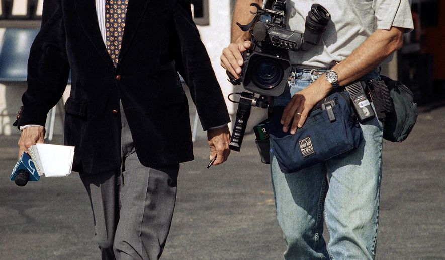 FILE - In this July 13, 1998 file photo, veteran KTLA television reporter Stan Chambers, left, and photographer Greg Hunter walk in Lawndale, Calif. Chambers, who had a front-row seat to earthquakes, fires and the life of the city since the 1940s died, Friday, Feb. 13, 2015, at home in Los Angeles after a long illness,  KTLA News Director Jason Ball said. He was 91. (AP Photo/Kevork Djansezian, File)