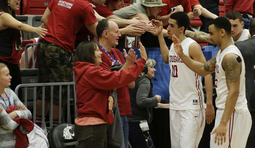 Washington State guards Dexter Kernich-Drew (10) and DaVonte' Lacy (25) celebrate the win against Arizona State with fans during the second half of an NCAA college basketball game, Friday, Feb 13, 2015, in Pullman, Wash. Washington State won 74-71 (AP Photo/Gary Breedlove)