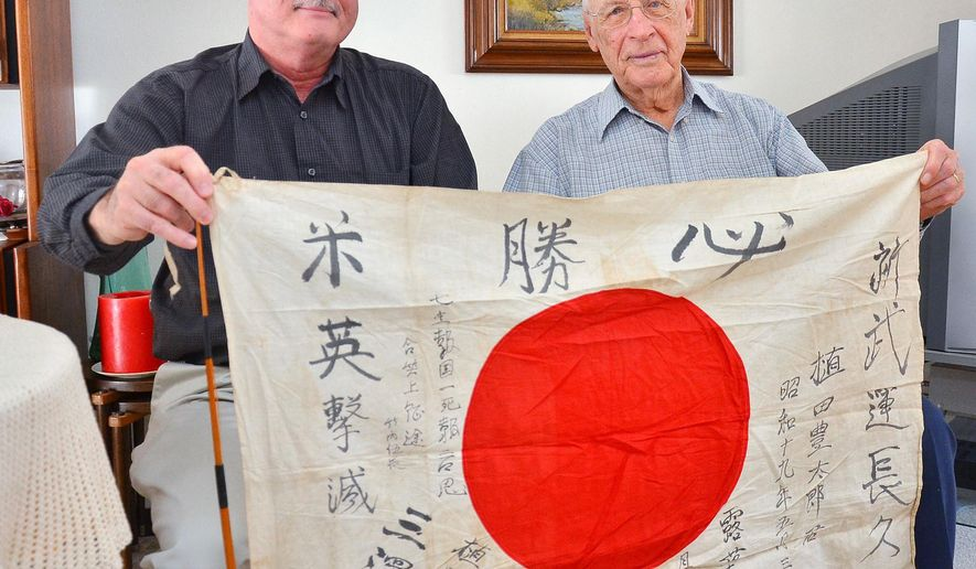 Bobby Harriosn, left, holds a Japanese flag that his father, Bob, right, found in an abandon hut in Malisa during World War II on Feb. 6, 2015  in Muscatine, Iowa. Harrison was part of the 1st Cavalry, 8th Regiment, 2nd Recon and was part of the group that followed Gen. Douglas MacArthur's orders to liberate the prisoners. (AP Photo/The Muscatine Journal, Beth Van Zandt)