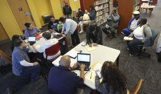In this photo made Thursday, Feb. 12, 2015, Affordable Care Act navigators hold an enrollment event at the Fort Worth Public Library in Fort Worth, Texas. (AP Photo/LM Otero)
