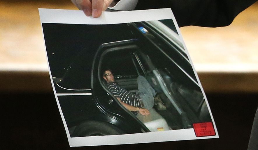 Erath County District Attorney Alan Nash carries a photo of former Marine Cpl. Eddie Ray Routh handcuffed in the back of a Lancaster Police car the night of his arrest, during Routh's capital murder trial at the Erath County, Donald R. Jones Justice Center in Stephenville, Texas,  Friday, Feb. 13, 2015. Routh, 27, of Lancaster, is charged with the 2013 deaths of former Navy SEAL Chris Kyle and his friend Chad Littlefield at a shooting range near Glen Rose, Texas. The photo, made by Texas Ranger David Armstrong, was offered as evidence by Nash. (AP Photo/The Fort Worth Star-Telegram, Paul Moseley, Pool)