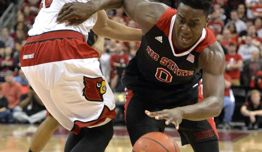 North Carolina State's Abdul-Malik Abu, right, drives around Louisville's Wayne Blackshear during the first half of an NCAA college basketball game, Saturday, Feb. 14, 2015 in Louisville, Ky. NC State won 74-65. (AP Photo/Timothy D. Easley)