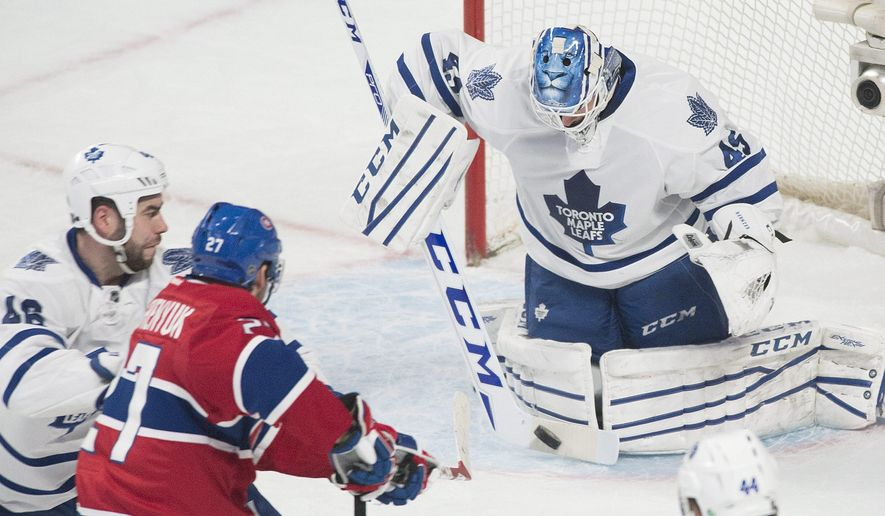 Toronto Maple Leafs goaltender Jonathan Bernier makes a save on Montreal Canadiens' Alex Galchenyuk, bottom, as Maples Leafs' Roman Polak, left, defends during the second period of an NHL hockey game, Saturday, Feb. 14, 2015, in Montreal. (AP Photo/The Canadian Press, Graham Hughes)