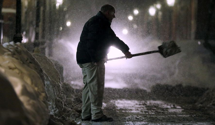 A man shovels snow on Beacon Hill in Boston, Saturday, Feb. 14, 2015. A blizzard warning was in effect for coastal areas from Connecticut to Maine on Saturday for a fourth major storm in less than a month, promising heavy snow and powerful winds to heap more misery on a region that has already seen more than 6 feet of snow in some areas. (AP Photo/Michael Dwyer)