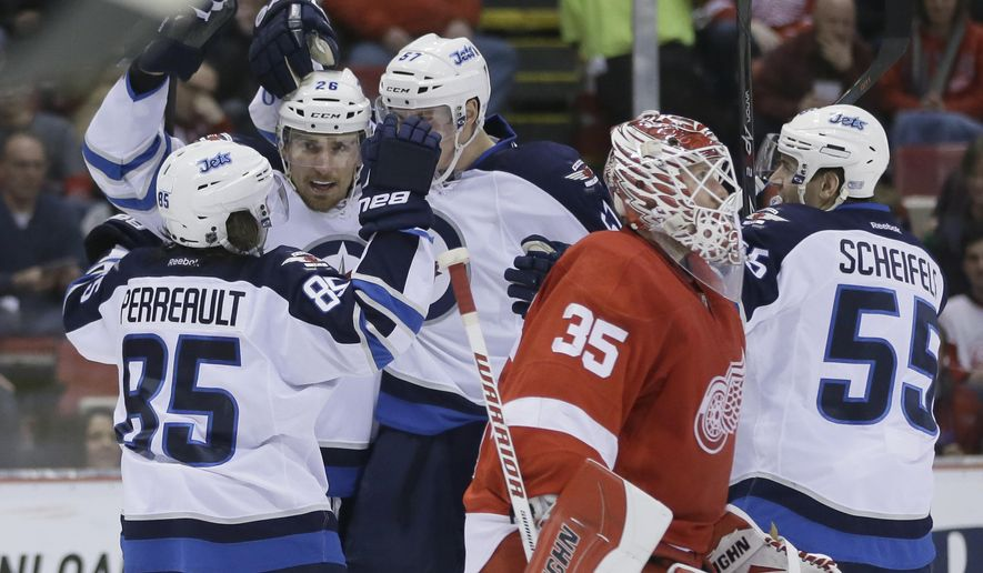 Winnipeg Jets right wing Blake Wheeler, second from left, is congratulated by teammates on his goal on Detroit Red Wings goalie Jimmy Howard (35) during the second period of an NHL hockey game, Saturday, Feb. 14, 2015 in Detroit. (AP Photo/Carlos Osorio)