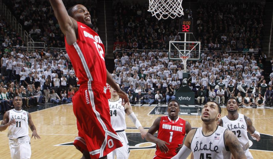 Ohio State's Sam Thompson (12) goes up for a dunk over Michigan State's Denzel Valentine (45) during the second half of an NCAA college basketball game, Saturday, Feb. 14, 2015, in East Lansing, Mich. Michigan State won 59-56. (AP Photo/Al Goldis)