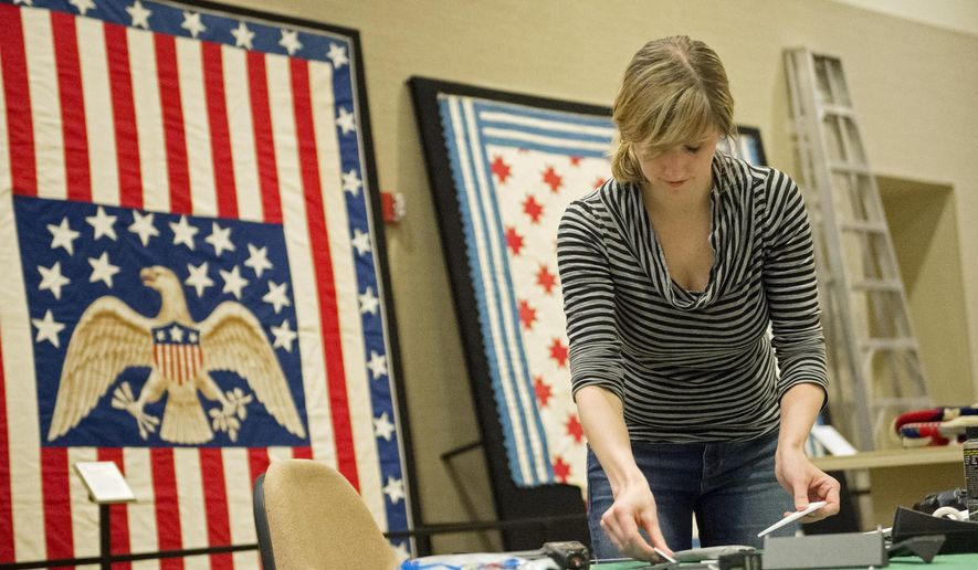 "In this Jan. 23, 2015 photo,  Artist Laura Mohr from the Nebraska History Museum helps set up a Civil War exhibit sponsored by the Nebraska History Museum in collaboration with the American Textile History Museum, a Smithsonian Institution, at the Great Plains Art Museum in Lincoln, Neb.   The exhibition, ""Homefront & Battlefield: Quilts and Context in the Civil War,"" fit with the museum's mission of historical education.   (AP Photo/The Journal-Star, Kristin Streff) LOCAL TELEVISION OUT; KOLN-TV OUT; KGIN-TV OUT; KLKN-TV OUT"