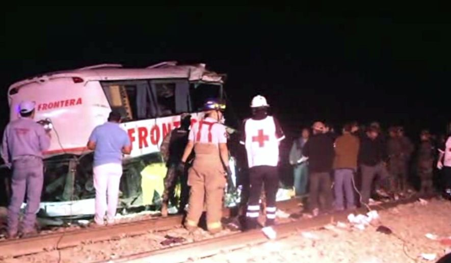 In this image made from Associated Press Television News video  emergency responders work at the scene of a bus and freight train collision Friday Feb. 13, 2015. The collision at a grade crossing in northern Mexico, killed at least 16 people and injured 22, according to a Mexican official. The official said the accident  Friday occured in the town of Anahuac, which is Tamaulipas state near the border city of Nuevo Laredo, across from Laredo, Texas. (AP Photo/AP Television)