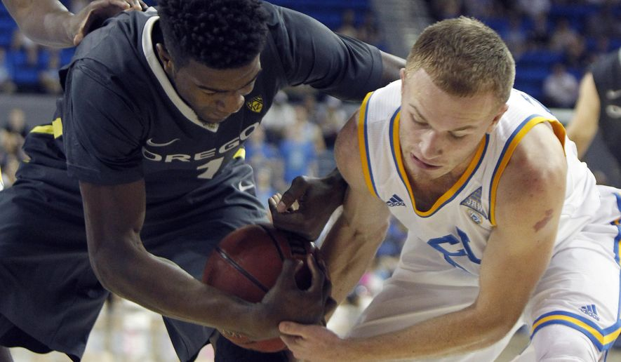 Oregon forward Jordan Bell, left, battles UCLA guard Bryce Alford for the ball during the first half of an NCAA college basketball game in Los Angeles, Saturday, Feb. 14, 2015. (AP Photo/Alex Gallardo)