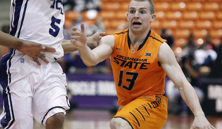 Oklahoma State guard Phil Forte III (13) looks for room against TCU guard Kyan Anderson (5) during the first half of an NCAA college basketball game, Saturday, February 14, 2015, in Fort Worth, Texas. (AP Photo/Brandon Wade)