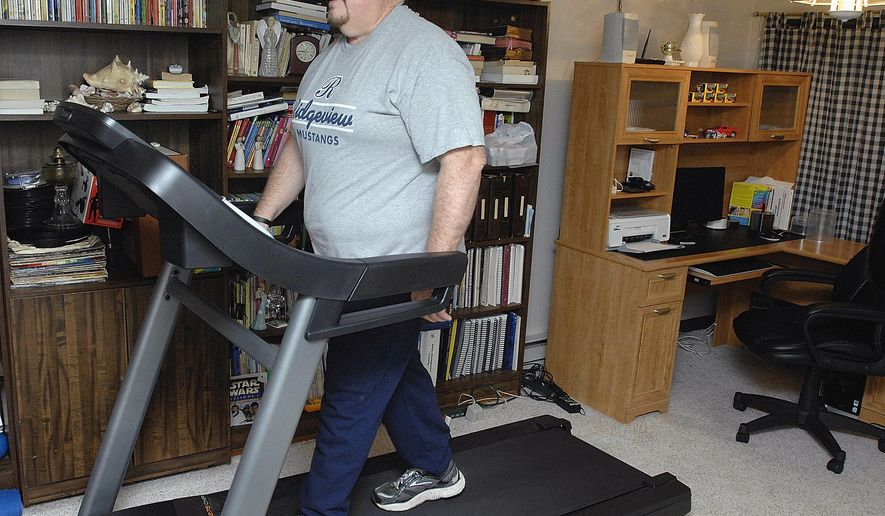 ADVANCE FOR USE SATURDAY, FEB. 14 AND THEREAFTER - In this Jan. 12, 2015 photo, Bob Barnes, of Colfax, Ill., warms up on the treadmill at his home. After Bob's heart attack a year ago while overexerting himself shoveling snow, exercise has been a priority.  (AP Photo/The Pantagraph, Lori Ann Cook-Neisler)