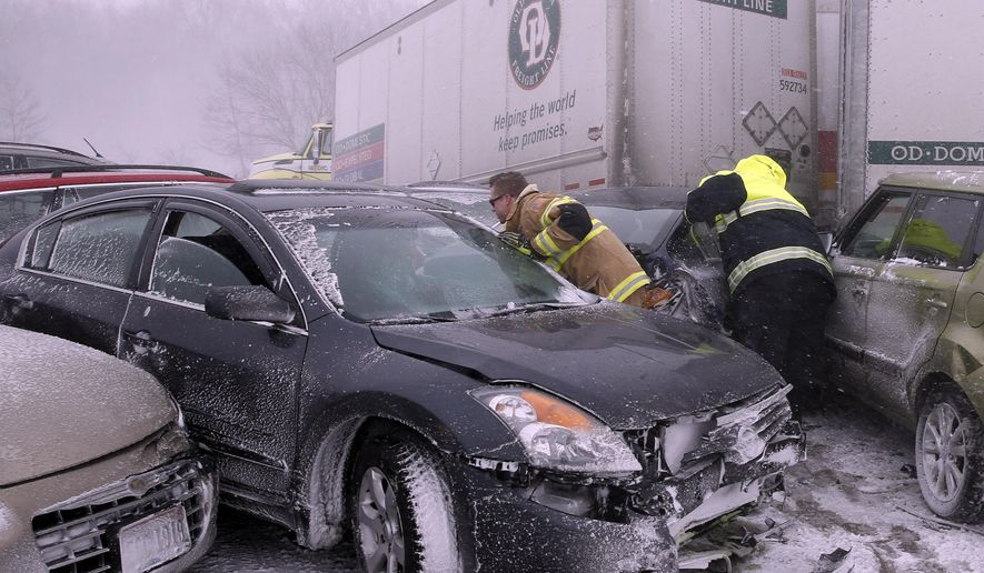 First responders check on occupants of a multi-vehicle accident in near white out conditions, blocking west bound I-70, Saturday, Feb. 14, 2015 west of Dayton, Ohio.  Heavy blowing snow is making travel difficult across Ohio and has caused quite a few accidents on the interstates. (AP Photo/Alex Brandon)