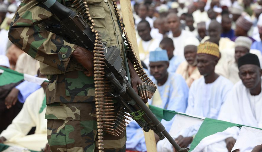 A Nigerian soldiers stand guard during Eid al-Fitr celebrations in Maiduguri, Nigeria, in this Thursday, Aug. 8, 2013, file photo. Nigeria's military on Saturday, Feb. 14, 2015, repelled an attack on a northeastern town by Boko Haram Islamic extremists who, as they retreated, warned residents not to participate in the country's elections in March. (AP Photo/Sunday Alamba, File)