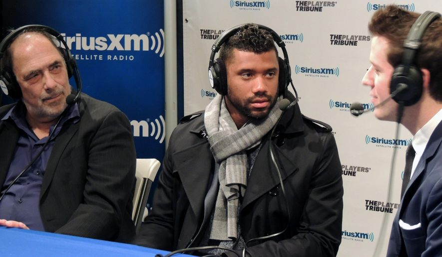 Seattle Seahawks' Russell Wilson, center, speaks to members of the media before a panel to launch Derek Jeter's new digital media company The Players' Tribune, Saturday, Feb. 14, 2015, in New York. (AP Photo/Nekesa Moody)