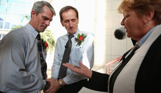 Milton Persinger (left) and Robert Povilat, both of Mobile, Alabama, get married at Government Plaza as the Rev. Sandy O'Steen from Cornerstone Metropolitan Community Church officiates. They were the first same-sex couple to get married in Mobile on Thursday. (Associated Press)