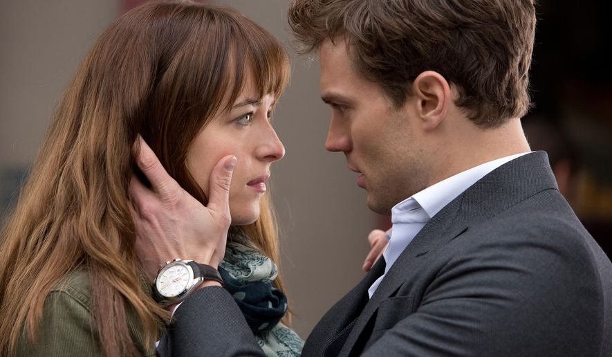 "In this image released by Universal Pictures and Focus Features, Dakota Johnson, left, and Jamie Dornan appear in a scene from the film, ""Fifty Shades of Grey.""  (AP Photo/Universal Pictures and Focus Features)"